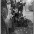 John Burroughs, author and naturalist, full-length portrait, standing, facing front, outside his home