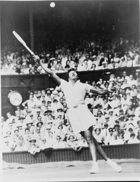 Althea Gibson, of New York, reaching high for shot during women's singles semifinal match against Christine Truman, of England, in All England Lawn Tennis Championships at Wimbledon, England, July 4, 1957