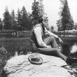 John Muir, full-length portrait, facing right, seated on rock with lake and trees in background