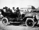 Eskimos, five adults and one infant, sitting in an automobile