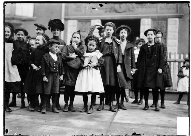 School strike, a group of children and a woman assembled on a sidewalk in front of a Tilden school entrance