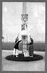 """Three women attaching """"Votes for women"""" poster to telephone pole"""