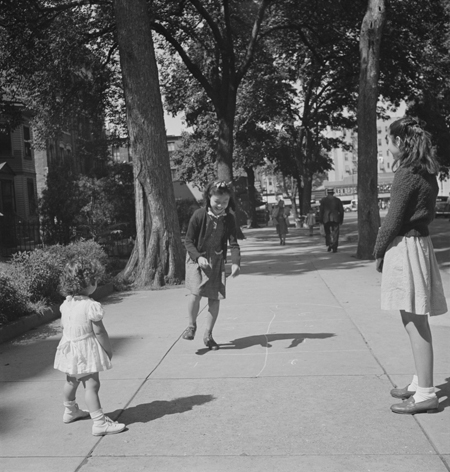 New York, New York. Chinese-American girl playing hopscotch with American friends outside her home in Flatbush