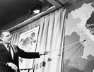 Sec. of Defense Robert McNamara pointing to a map of Vietnam at a press conference