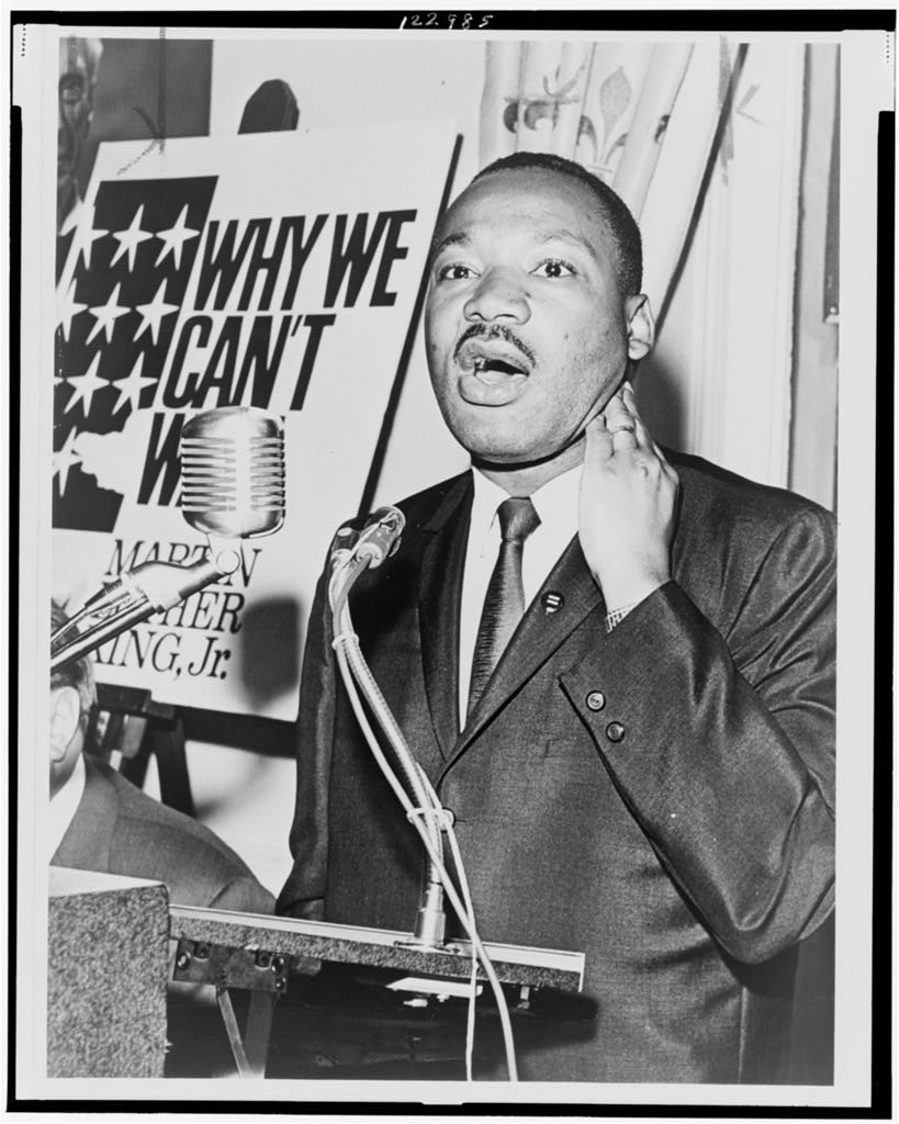 Martin Luther King, Jr., three-quarter-length portrait, standing, facing front, at a press conference