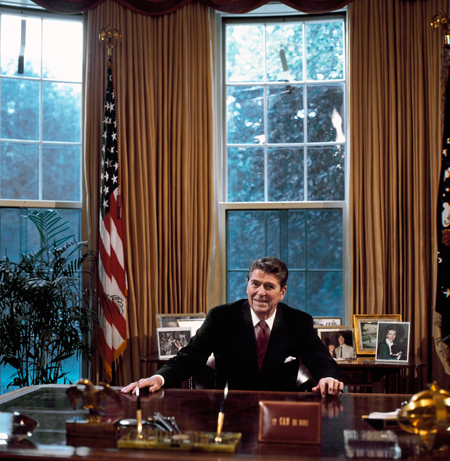 President Ronald Reagan at his desk in the Oval Office