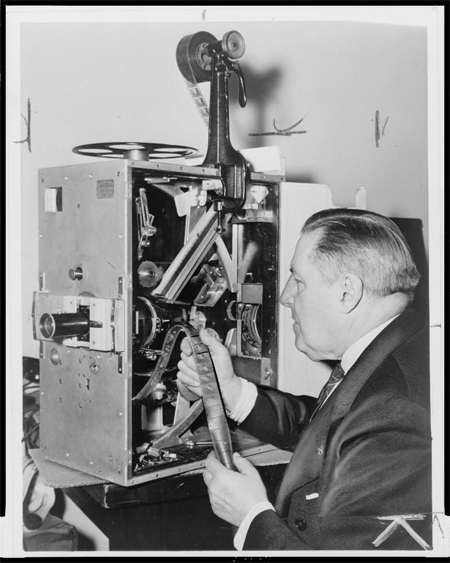 Billy Bitzer seated at movie projector