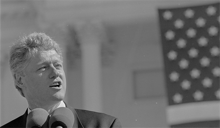 President Bill Clinton, head-and-shoulders portrait, speaking into a microphone in front of the U.S. Capitol