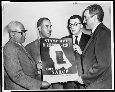 Holding a poster against racial bias in Mississippi are four of the most active leaders in the NAACP movement