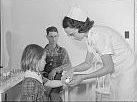 Nurse treating child in health clinic